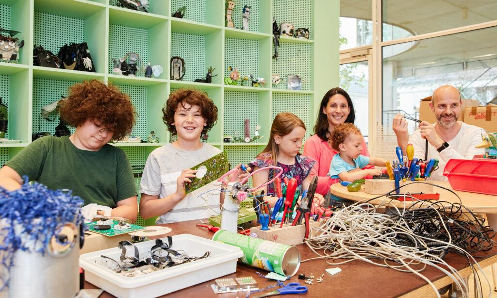 Eine Familie mit vier Kindern im Werkstatt im Museum.